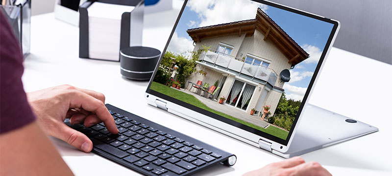 Person looking at homes on laptop-beware of real estate scams